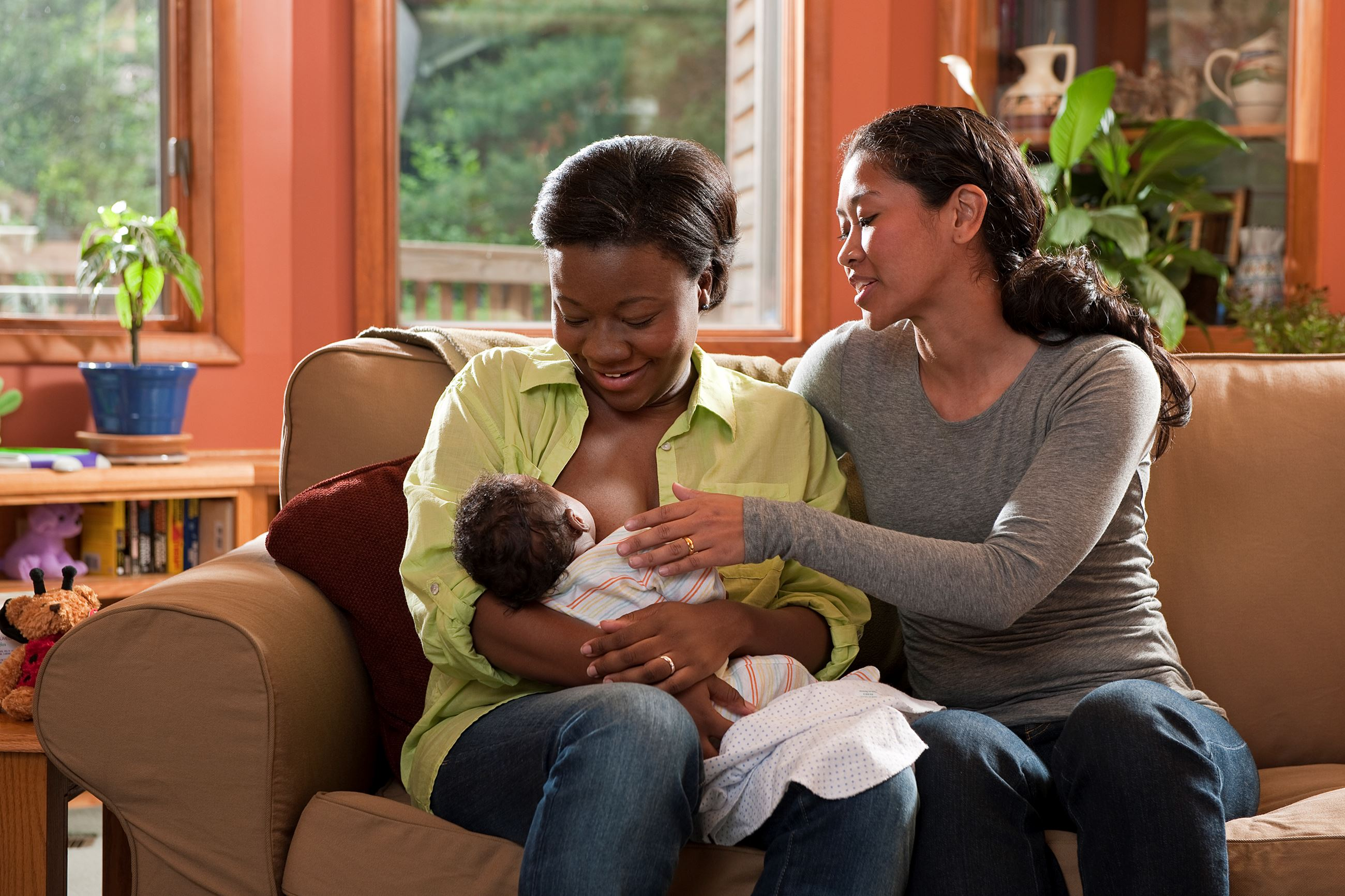Women Sit Together on Counch While One Breastfeeds a Baby