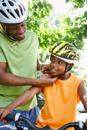 Man and Boy on Bike Wearing Bicycle Helmets