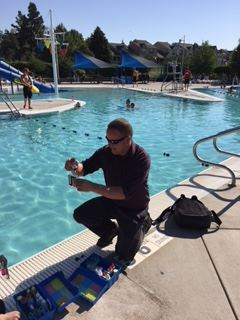 Man Kneeling, Conducting Tests by Side of Pool