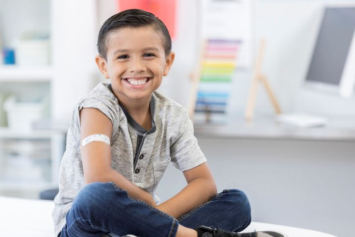 Boy sitting on an exam table with band aid on his arm smiling
